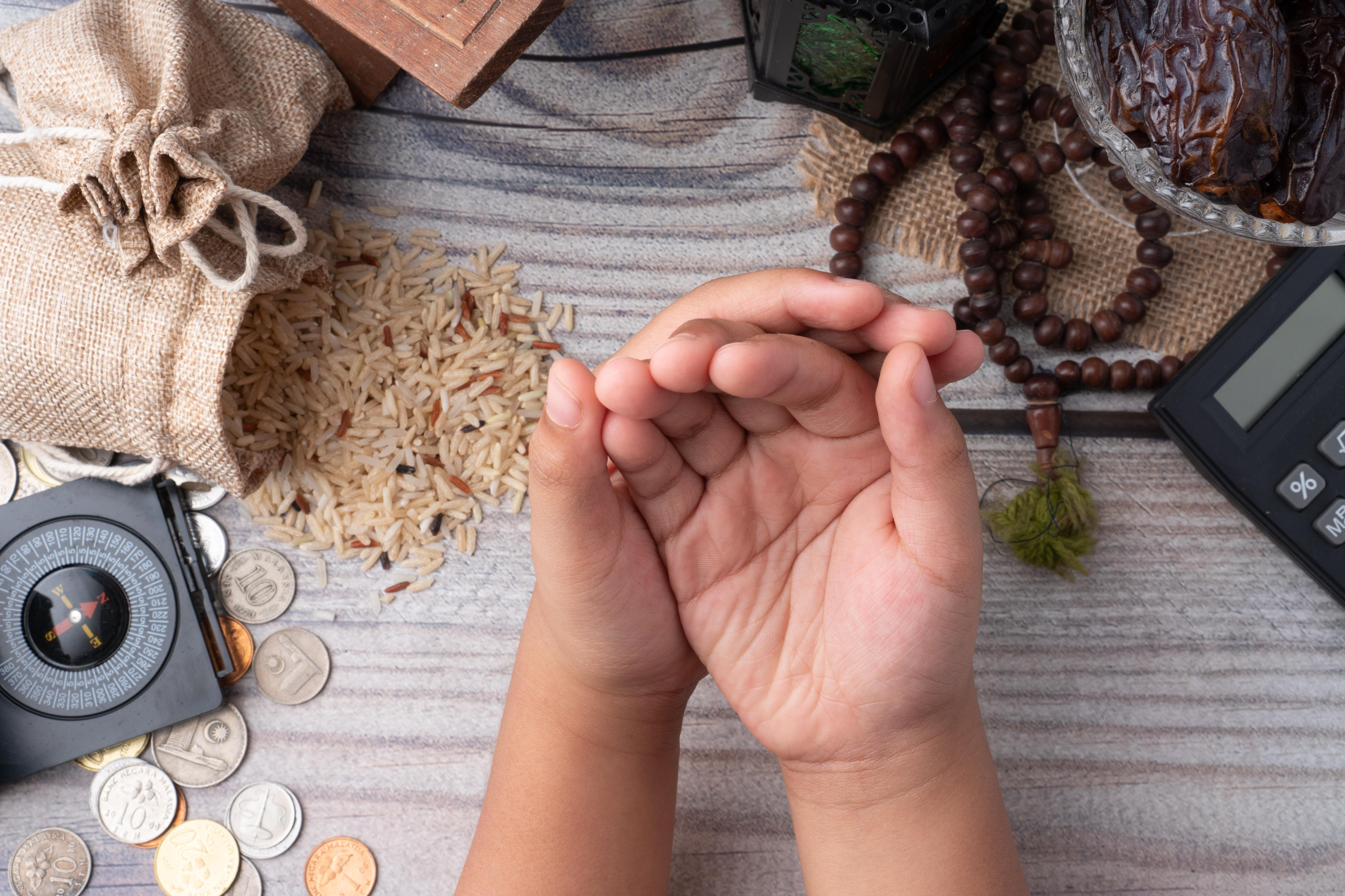 Child's hands cupped with rice, money and rosary in the background