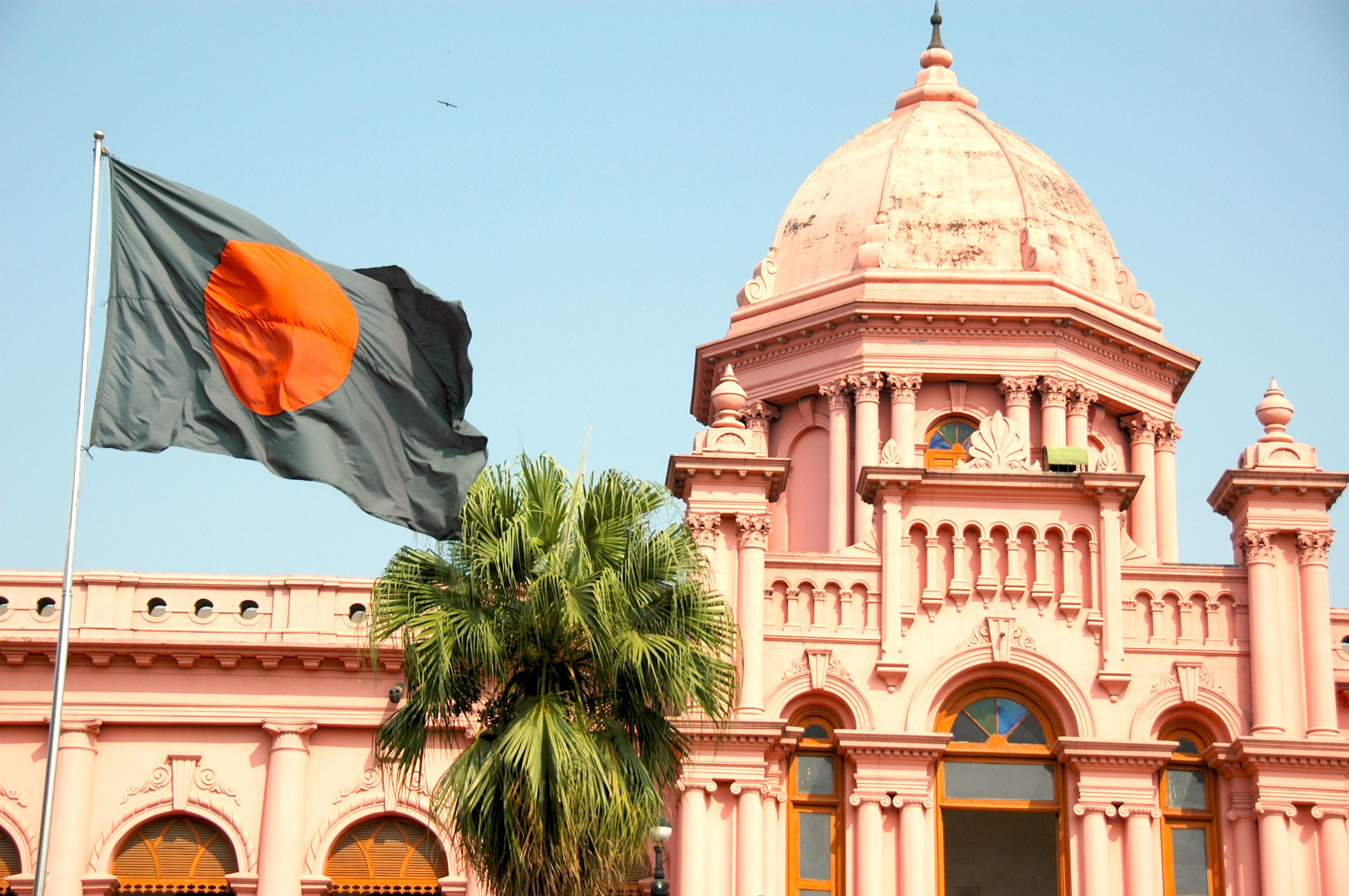 Colonial building with the Bangladeshi flag waving in front of it