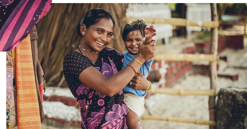 Village lady carrying a toddler waving at the camera