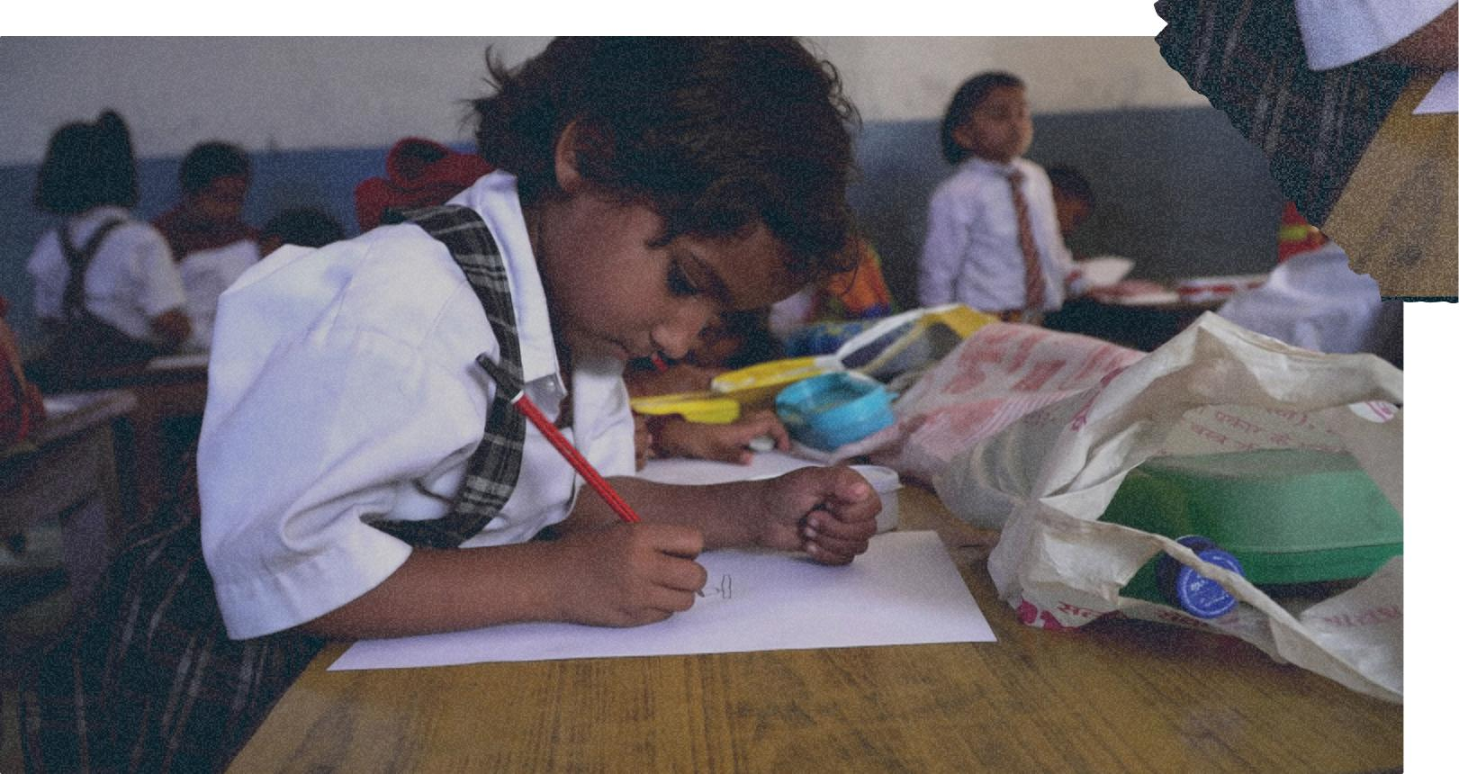Child writing on paper with pencil in class